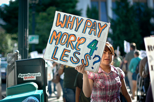 a protest sign says why pay more 4 less?