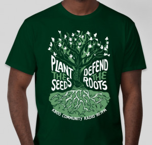 """Green t-shirt worn by model. Shirt has an illustration of a tree with text surrounding the tree reading """"Plant the Seeds, Defend the Roots"""""""