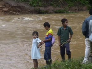 Children standing by a rushing river in Nicaragua