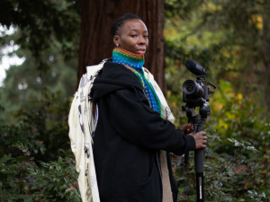 Kalimah Abioto standing outdoors with camera and tripod