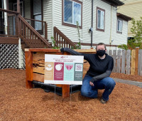 Amethyst Devlin squats next to a a mobile orchard box. The box is cedar wood on top of half a large plastic container and has a fruit tree planted in it.