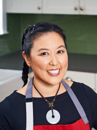 Michelle Tam of NomNom Paleo poses in an apron.
